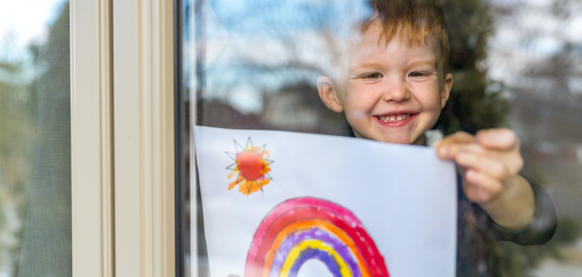 Young boy, smiling, hanging up his drawing of a rainbow up to the window.