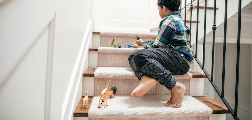 Young boy playing on the stairs with his toys.