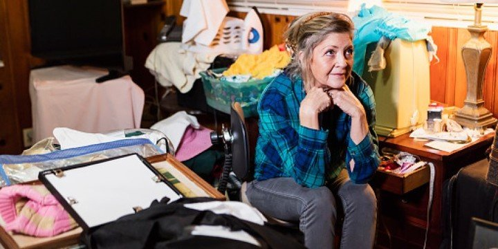 Woman sitting in a cluttered room