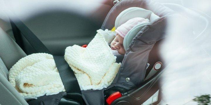 Newborn baby snug in a car seat
