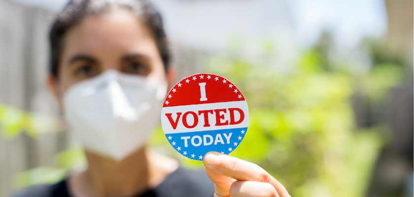 "Woman wearing a mask holding an ""I voted today"" sticker."