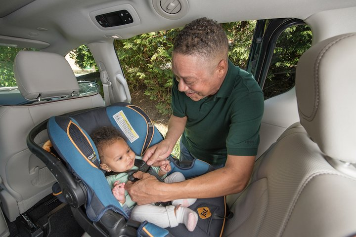 Adult buckles in young baby to car seat that is rear-facing