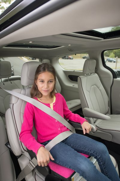 Young female child sits in booster seat