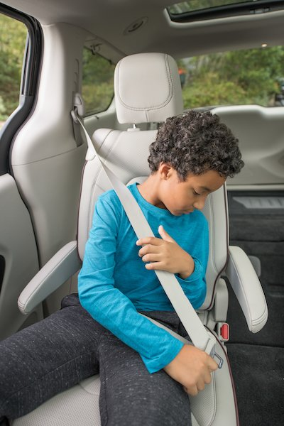 Male child displays properly using a seat belt