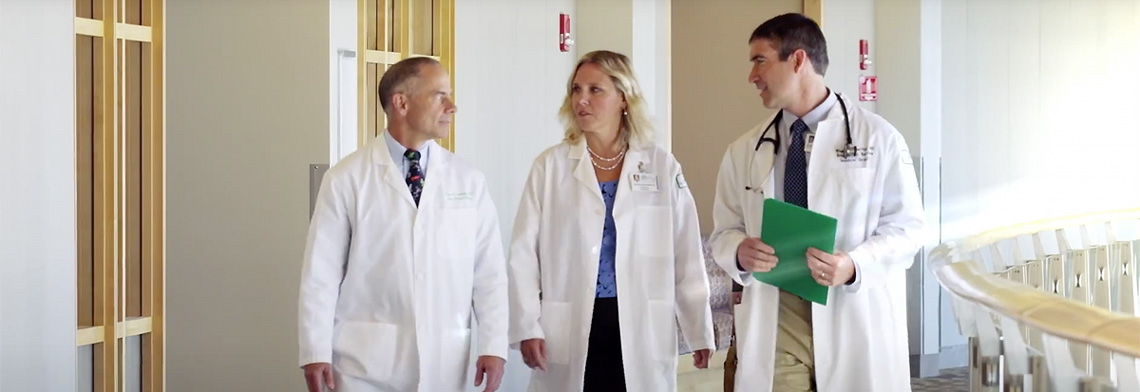 Three providers talking while walking along UVM Med Center hallway