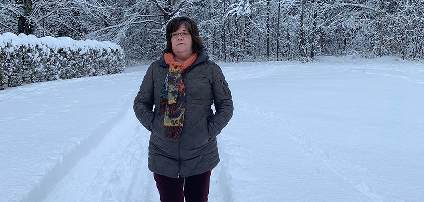 Woman walking outside inside the snow.