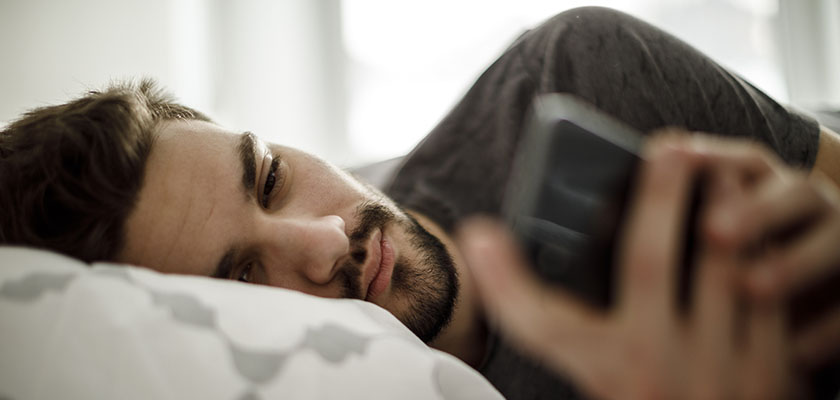 Man lying on his bed staring at his phone.
