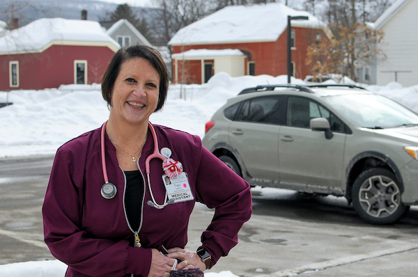A nurse standing in a parking lot smiling at the camera. She is wearing a maroon jacket and pink stethoscope, and resting both hands on her left hip.