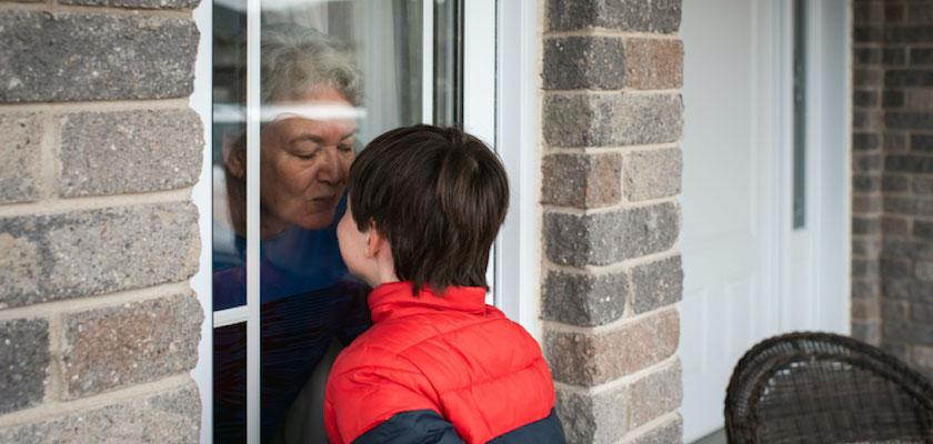 Grandmother kissing grandson through a window pane.
