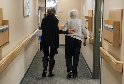 An elderly cardiology patient walking away from the camera down the hall. A women in her 60s has her hand on her back, guiding her.