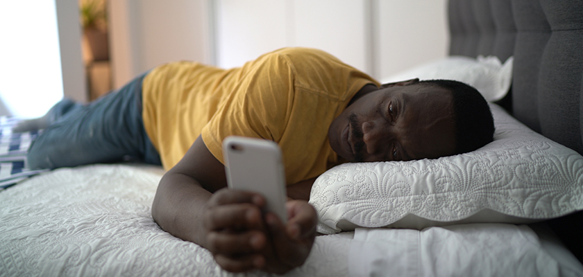 A man lying on his bed staring at his phone, he is African-American and wearing a yellow shirt and blue jeans.