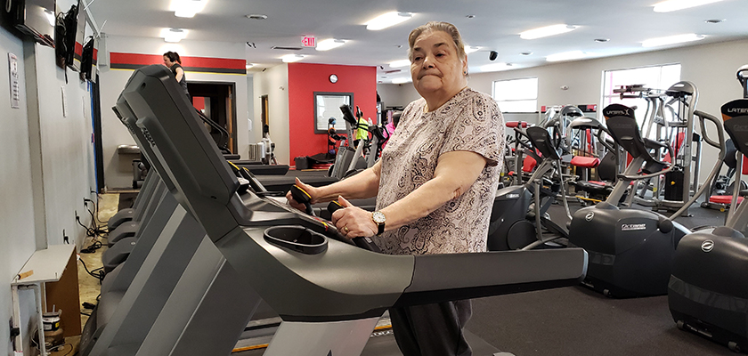 A women in her 70s standing on a treadmill looking off to the left of the camera.