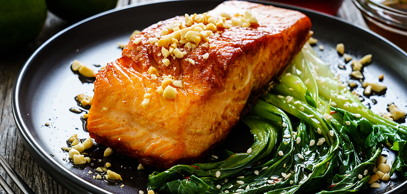 Salmon on a bed of swiss-chard sitting on a black plate.