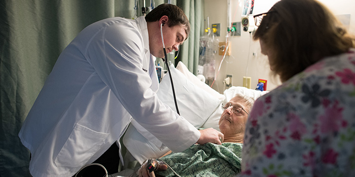 Doctor listening to elderly man's heart with stethoscope