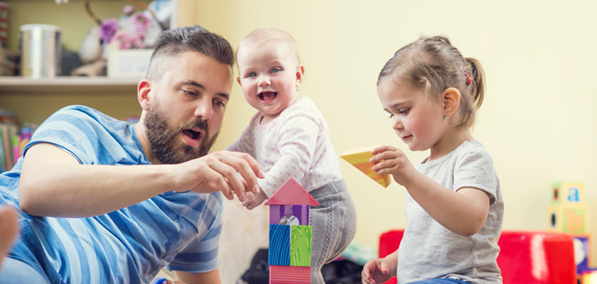 Father playing blocks with children