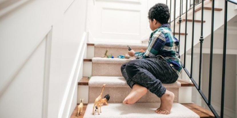 Little boy playing with toys on stairs