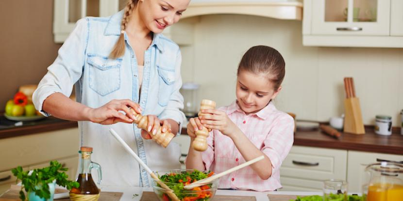 Mother and daughter prepare a salad together
