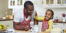 Father and daughter cook dinner together