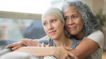 Elderly woman holding a young girl with cancer