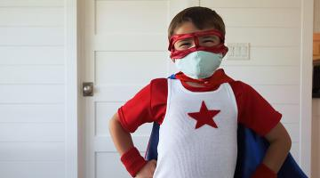 Child dressed as a super hero wearing a mask
