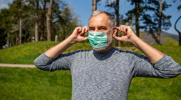 Man standing outside in a park putting on a mask,
