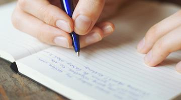 A close up of someone writing in their journal.