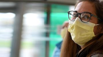 Medical Center female nurse wearing mask smiling at the camera. She is wearing black round glasses and yellow disposable mask.