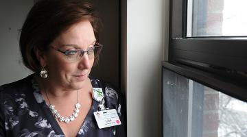 Portrait of Lisa Woodworth looking out the window. She is wearing glasses, a necklace and blouse.