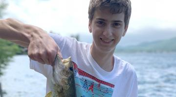 Teenage boy smiling at the camera holding up a fish he caught. A lake is in the background.