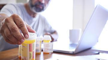 Older man looking at medication bottles while sitting at his laptop.