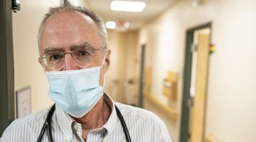 Headshot of Dr. Peter Van Buren, a cardiologist in his 60's, wearing a mask and standing in the hallway of the Medical Center.